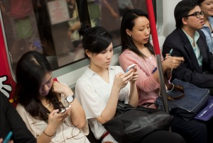 epa03241615 Commuters use smartphones while riding a subway train in Hong Kong, China, 30 May, 2012. An online poll of 1,532 people showed that nearly 95 percent of the respondents experience severe neck and back problems for spending too much time hunched over their gadgets such as iPads, iPhones and other tablets. The Hong Kong Multisports Association, which conducted the survey from April 23 to May 6, said one out of three use their devices for more than four hours a day while 57percent do the same on their computers. According to the poll, one of the main reasons for the growing incidence of chronic back and neck pains is people using their devices for long periods and maintaining a wrong posture, including keeping their heads down.  EPA/JEROME FAVRE (Newscom TagID: epaphotos422092.jpg) [Photo via Newscom]