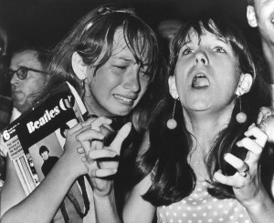 Two girls attending the Beatles concert in Philadelphia, USA on August 16, 1966, display mixed emotions as the band performed before a crowd of about 21,000 people. Barricades were erected about 150 feet from the stage and police kept the lively set under control with an occasional fan trying to climb the barricades. (AP Photo)