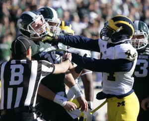 Michigan's Delano Hill, right, shoves Michigan State quarterback Connor Cook during the first quarter of an NCAA college football game, Saturday, Oct. 25, 2014, in East Lansing, Mich. Hill was penalized on the play. (AP Photo/Al Goldis)