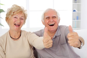 Happy mature couple showing ok and laughing.