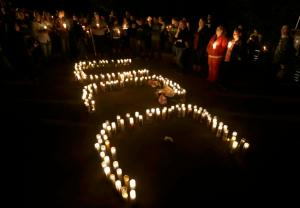 Candles spelling UCC for Umpqua Community College, are displayed at a candlelight vigil for those killed during a fatal shooting at the school, Thursday, Oct. 1, 2015, in Roseburg, Ore. (AP Photo/Rich Pedroncelli)