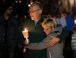 Kevin Crawford embraces his wife, Pam, during a candle light vigil for those killed during a shooting at Umpqua Community College, Thursday, Oct. 1, 2015, in Roseburg, Ore. (AP Photo/Rich Pedroncelli)