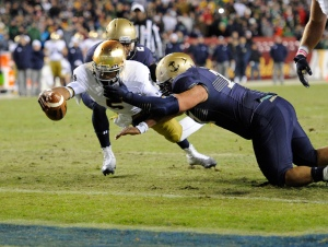 Notre Dame quarterback Everett Golson (5) dives for the end zone to score a touchdown against Navy safety Parrish Gaines (2) and others during the second half of an NCAA college football game, Saturday, Nov. 1, 2014, in Landover, Md. Notre Dame won 49-39. (AP Photo/Nick Wass)