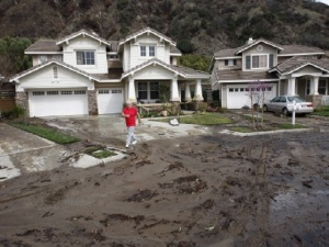 AZUSA, CA - MARCH 1: Ed Heinlein walks in front of his house that is threatened with a possible major landslide from the burned hillsides above as a storm brings rain in the midst of record drought on March 1, 2014 near Azusa, California. The rain offers some relief to the dry conditions but is not expected to be enough to break the historic drought. A drought-related unseasonal wildfire, the Colby Fire, was accidentally ignited in the dry chaparral vegetation in January, destroying homes and sending thousands fleeing. The charred and denuded hillsides are threatening the homes of about a thousand evacuated residents with rain-loosened mud-ash debris flows. (Photo by David McNew/Getty Images)