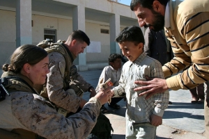 Petty Officer 2nd Class Bridget Shanahan, a corpsman with Shock Trauma Platoon, 2nd Combat Logistics Battalion, and Lance Cpl. Michael Johnson, a wireman with Communications Platoon, Headquarters and Service Company, 2nd Battalion, 25th Marine Regiment, Regimental Combat Team 5, hand out stuffed animals to a second grade student at Houran Primary School in Rutbah, Iraq, Dec. 2. Not only was this the first time most of the children at Houran had ever interacted with Coalition forces, but it was an education in the integral role that females serve in the U.S. military.