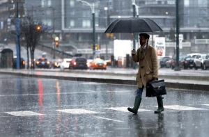 A man walks across Spadina Ave as Toronto begins a few days of wet weather. Randy Risling /Toronto Star
